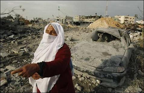 Una mujer camina entre los escombros y los destrozos en Gaza. REUTERS