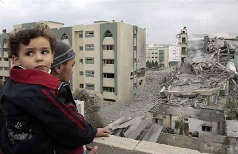 Un hombre con un niño mirando a la Universidad Islámica de Gaza destruída por Hamas. REUTERS