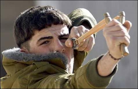 Un palestino utiliza un tirachinas para tirar piedras a las tropas israelíes. REUTERS