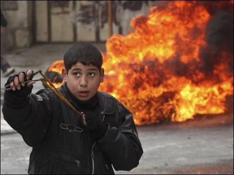 Un niño palestino usa un tirachinas durante los enfrentamientos con las tropas israelíes en una manifestación contra las hostilidades israelíes en Gaza hoy 29 de Diciembre.