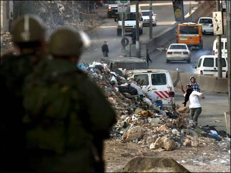 Soldados israelíes vigilan a los manifestantes palestinos que tiran piedras durante una manifestación en el punto de control cisjordano de Kalandia, al norte de Jerusalén el 29 de diciembre de 2008. Israel prosiguió hoy por tercer día consecutivo los bombardeos sobre Gaza, que han provocado más de 320 muertos y más de 1.400 heridos y aprobó una movilización de tropas que podría ser el preludio de una operación terrestre en la franja palestina. El gobierno israelí ha denominado a esta operación como 'Plomo Fundido'.