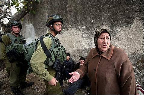Una mujer ruega a unos soldados israelíes que liberen a su hijo, que fue arrestado junto con otros jóvenes por arrojar piedras presuntamente durante un acto de protesta contra los ataques aéreos israelíes sobre Gaza, en la ciudad cisjordana de Hebrón el martes 30 de diciembre. EFE