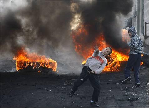 Jóvenes palestinos tiran piedras contra la policía y los vehículos militares en Jerusalén para protestar contra el ataque de Israel. REUTERS