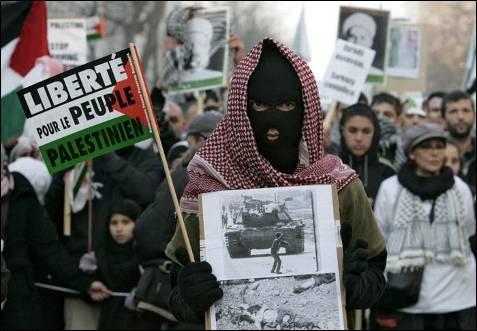 Una persona sostiene dos fotografías durante un acto de protesta contra la ofensiva israelí en la Franja de Gaza, en París, Francia, hoy sábado 10 de enero. LUCAS DOLEGA (EFE)