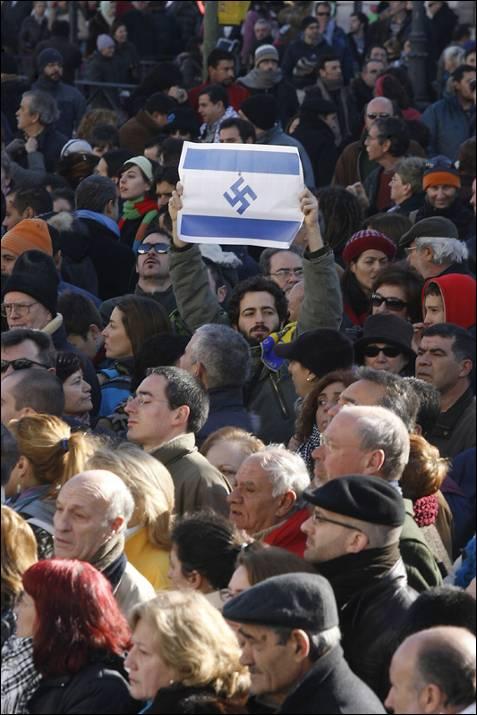 Un partipante en la manifestación a favor del pueblo palestino y de condena a los ataques israelíes contra la franja de Gaza que han causado ya más de 800 muertos, que recorrió hoy el centro de Madrid, entre la plaza de Cibeles y la puerta del Sol, y a la que asistieron miles de personas, despliega una bandera de Israel con una esvástica en el lugar de la estrella de David.