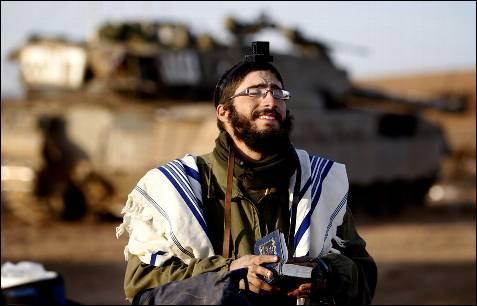 Un soldado israelí reza cerca de tanques y unidades preparadas para entrar en la franja.