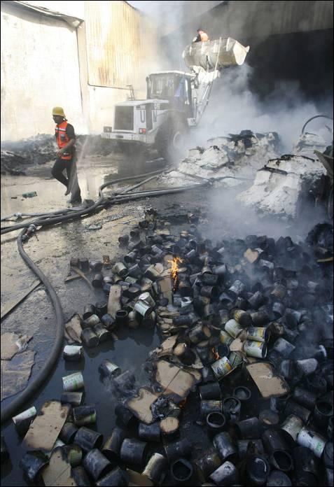 Bomberos palestinos extinguen el fuego en la sede de Naciones Unidas atacada por Israel, en la que se almacenaban alimentos y ayuda humanitaria.