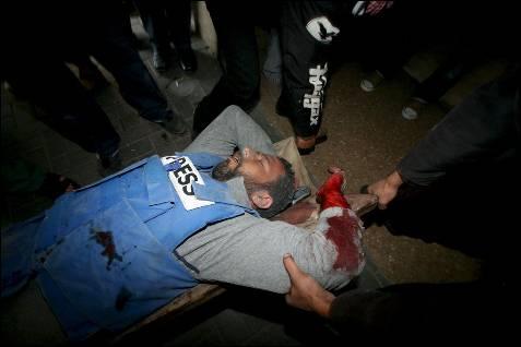 Doctores palestinos atienden al periodista Mohammed al Sosse tras resultar herido en el ataque israelí a un centro de prensa internacional.