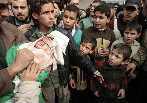 Palestinos de Gaza transportan el cuerpo de Asad, el hijo de un año del líder de  Hamás Nizar Rayyan, objetivo de uno de los bombardeos israelíes que murió junto a 11 de sus familiares. MOHAMMED SALEM / REUTERS