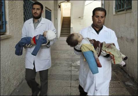 Doctores palestinos llevan los cadáveres de dos niños abatidos por un tanque del ejército israelí, en el tercer día de la invasión terrestre y décimo desde que Israel atacó la Franja, a la morgue del hospital de Shifa, en Gaza. SUHAIB SALEM / REUTERS