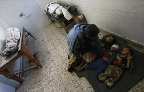 Magdi al-Samuli junto a los cadáveres de sus hijos, que murieron bajo el fuego de un tanque israelí. Hoy lunes, al menos cinco niños han muerto en dos ataques, según fuentes médicas palestinas. MAHMUD HAMS / AFP