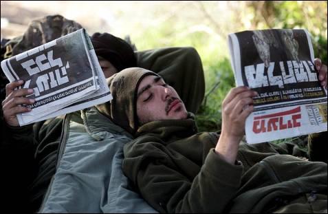Soldados israelíes descansan leyendo un periódico después de una operación militar en la Franja de Gaza. Al menos 23 palestinos, todos ellos civiles, han muerto hoy (5 de enero) en distintos bombardeos israelíes en la franja de Gaza. KOBI GIDEON / EFE