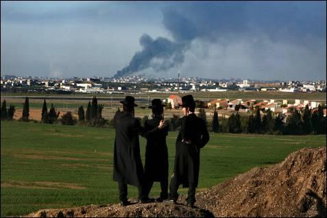 Judíos ultraortodoxos contemplan los bombardeos sobre Gaza desde una colina cercana. PAVEL WOLBERG / EFE