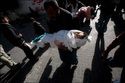 Dos hombres trasladan el cuerpo sin vida de dos menores que murieron en el bombardeo israelí en el colegio Al Fakhoura de la Agencia de las Naciones Unidas para los Refugiados (UNRWA), en el campo de refugiados de Yebalia de Gaza, donde el 6 de enero murieron 43 personas y más de un centenar resultaron heridas. MOHAMMED SABER / EFE