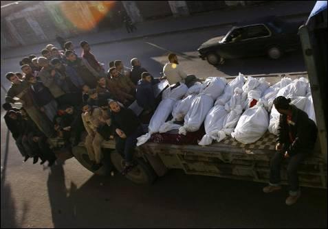 Habitantes de Gaza transportan los cuerpos de 13 palestinos de la misma familia, siete de ellos niños, asesinados en un bombardeo israelí sobre una casa que pertenecía a un militante de Hamás. MHAMUD HAMS / AFP