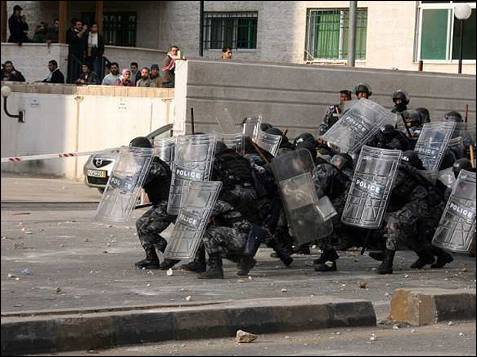 La Policía se protege contra las piedras que jordanos y palestinos les lanzan como protesta por los ataques israelíes perpetrados en la Franja de Gaza.AFP PHOTO/AWAD AWAD