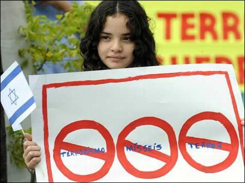 Una niña brasileña sostiene una bandera de Israel y un afiche en contra del terrorismo durante un acto de protesta en contra del movimiento palestino Hamás hoy, 9 de enero de 2009, frente a la Embajada de Israel en Brasilia (Brasil). El gobierno brasileño, que ha condenado severamente la ofensiva israelí en Gaza desde el pasado 27 de diciembre, viene realizado gestiones diplomáticas para intentar organizar una cumbre multilateral que encuentre una salida pacífica al conflicto. EFE/FERNANDO BIZERRA JR