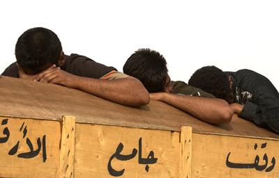 Los hermanos de una víctima de la violencia lloran su muerte en Bagdad en 2006. - AP