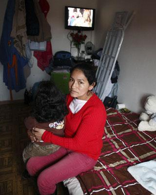 Paola, junto a su hijo, en la habitación familiar.
