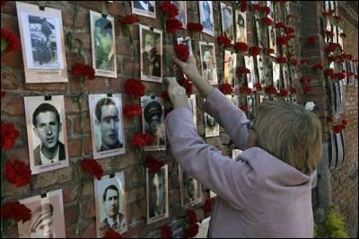 Una mujer coloca flores cerca de la fotografía de su familiar fallecido en la tapia del antiguo cementerio del Este en Madrid.