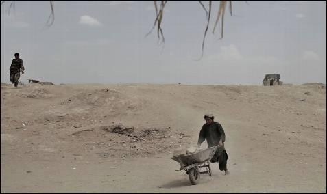 Un chaval afgano transporta una carretilla con ladrillos cerca del  destacamento de los marines en Marjah.