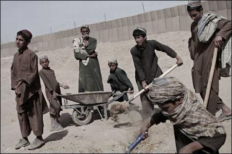 Los niños remueven arena para hacer cemento para construir un  muro.