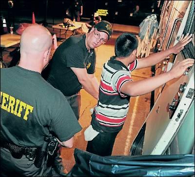 Dos agentes detienen a un inmigrante irregular.
