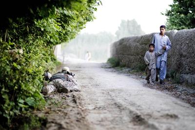Dos niños afganos pasan junto a un soldado del contingente alemán de las tropas de la OTAN en Afganistán, cerca de Kunduz. - AFP