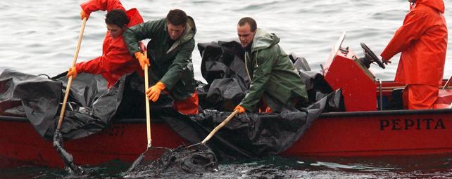Pescadores recogen fuel frente a la costa de Aguiño en diciembre de 2002. AFP