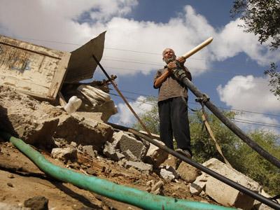 Un campesino palestino inspecciona el pozo de agua destruido por un ataque israelí en Rafah (Gaza).