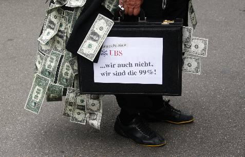 Una persona porta un maletín lleno de dinero delante de banco UBS en Zurich, Suiza. Un bróker de este banco causó  pérdidas por 1500 millones de euros al realizar actividades irregulares y provocó la dimisión del Consejero Delegado.