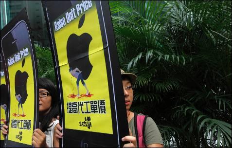 Activistas sindicales portan carteles con la famosa manzana de Apple llamando a la revuelta en la bolsa de Hong Kong.-