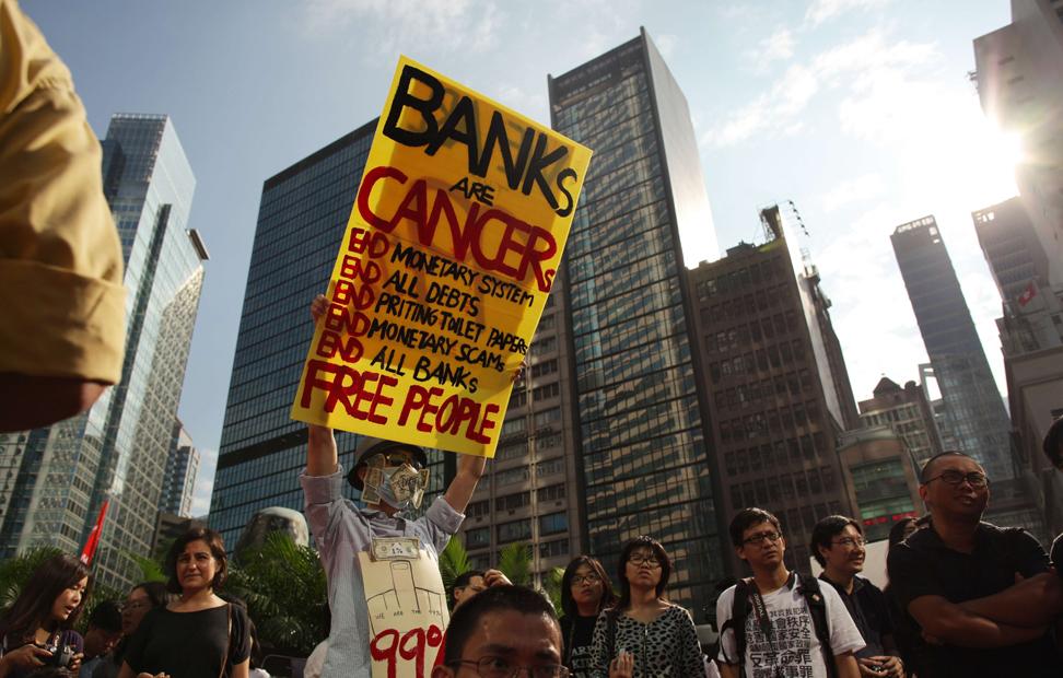 Un manifestante porta un cartel contra el sistema bancario en Honk Kong.-
