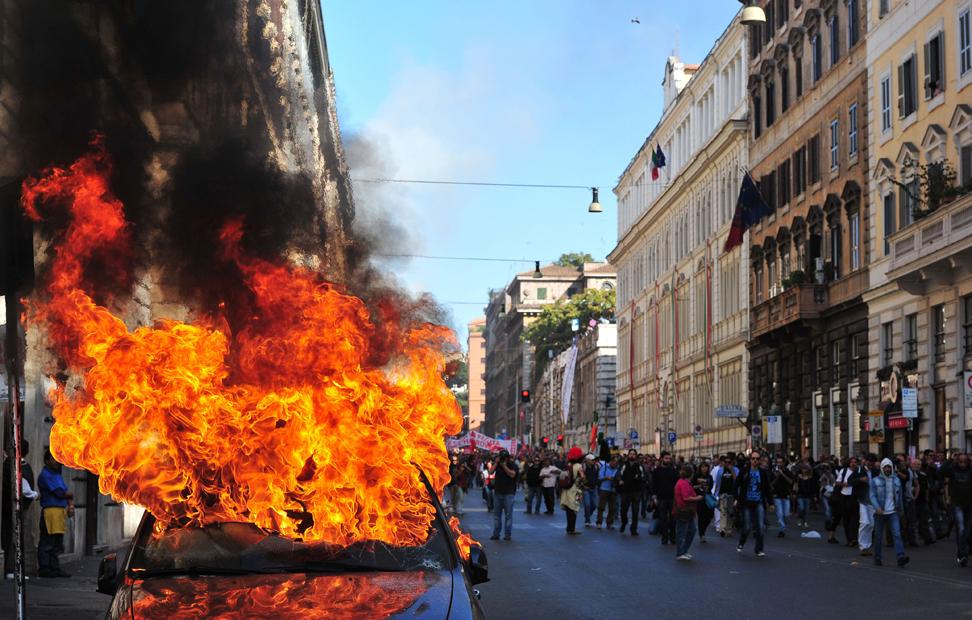 Un coche arde en la manifestación de Roma, Italia. Decenas de miles de personas han marchado por las calles de la capital italiana.-