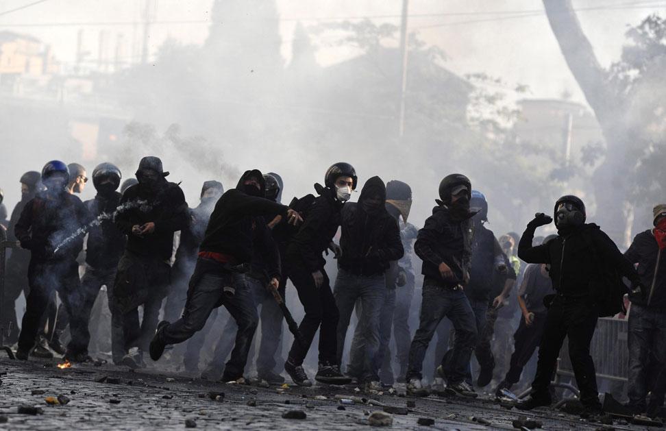 Un grupo de encapuchados lanza piedras contra la policía durante los incidentes que han tenido lugar en Roma