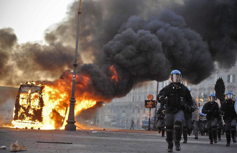 La policía italiana cargó contra indignados que incendiaron vehículos, y bancos y les arrojaban piedras