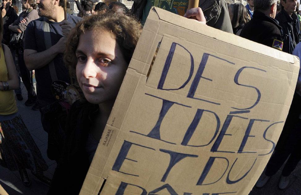 Jóvenes con carteles durante la manifestación de indignados convocada en París
