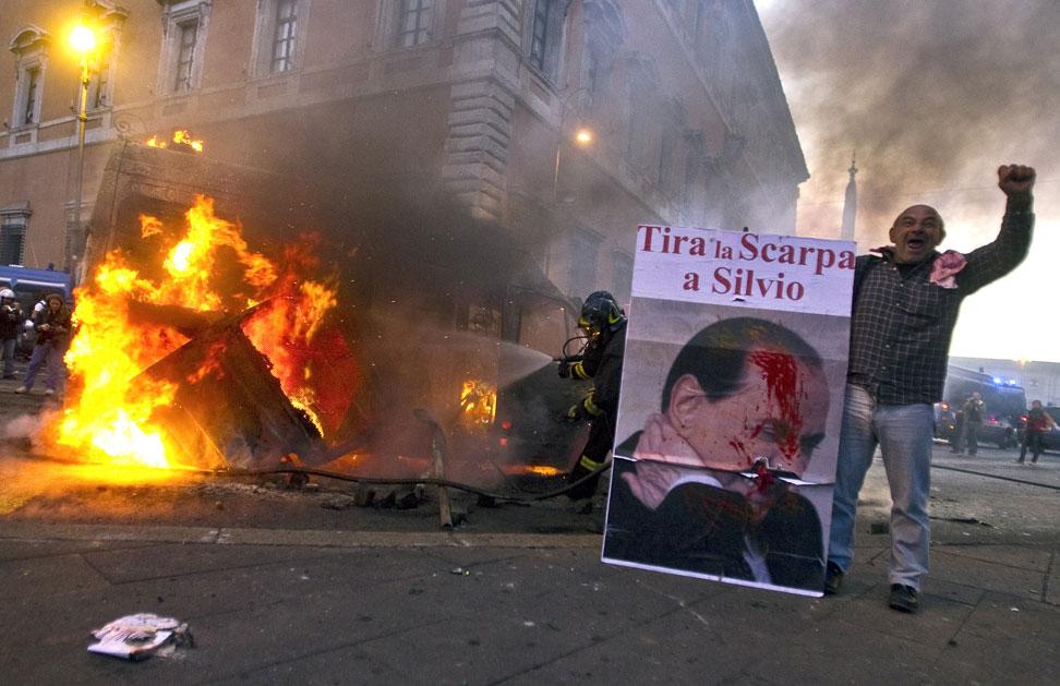 Un italiano levanta el puño fren a un coche de policía ardiendo