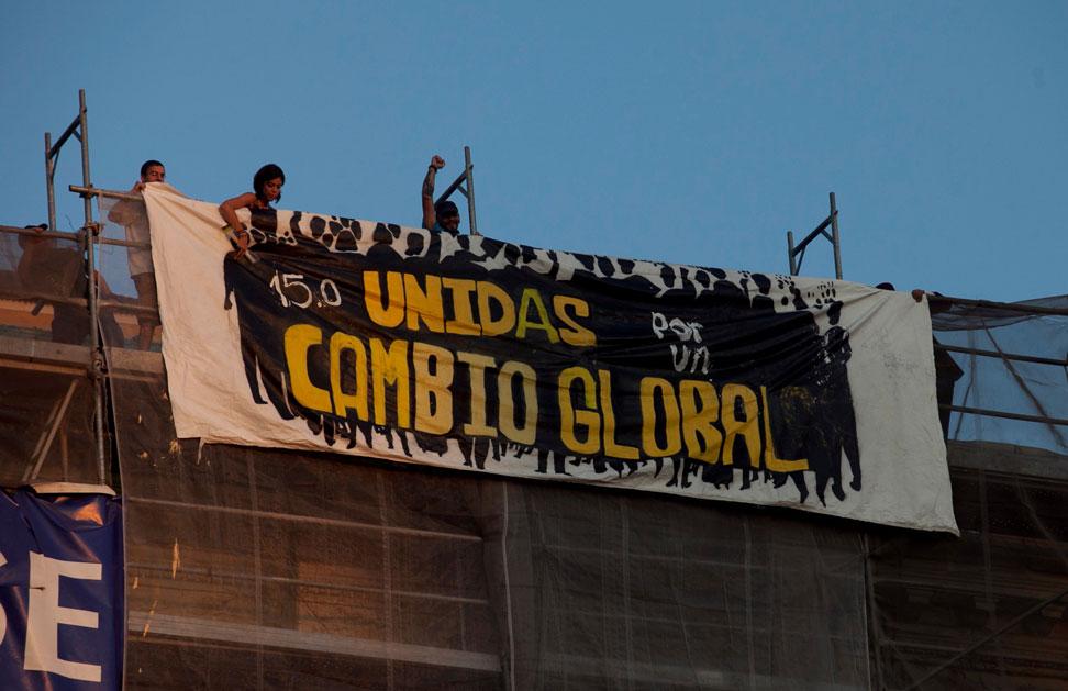 Jóvenes indignados despliegan una pancarta en un andamio de Sol