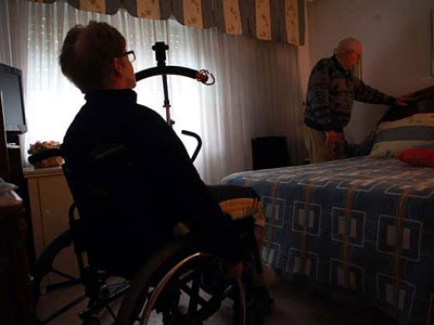 Juan Francisco, de 75 años, prepara la cama para su mujer, Ramona, de 68 y con discapacidad.-