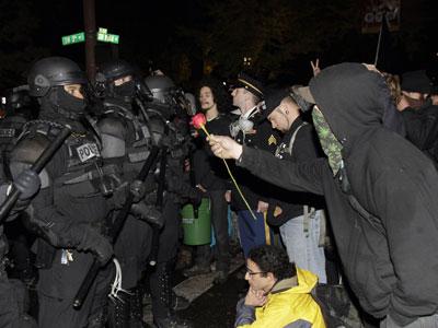 Un indignado ofrece una rosa a los policías que desalojaron el domingo el campamento de Portland.-