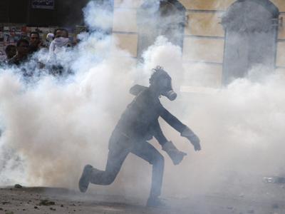 Un egipcio corre entre los gases lacrimógenos lanzados por la Policía. EFE