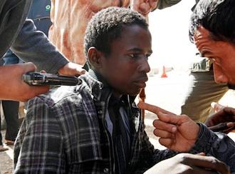 Rebeldes libios detienen en un puesto de control en Ras Lanuf a un joven negro acusándolo de colaborar con las milicias de Gadafi. Reuters-Archivo