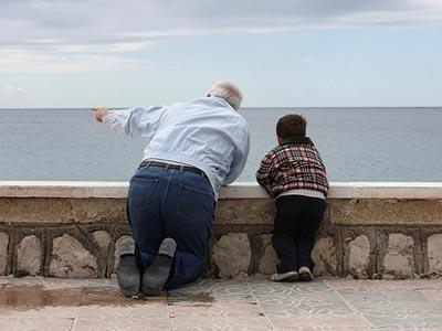 Un abuelo mirando al mar junto a su nieto.