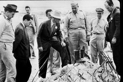 El físico Robert Oppenheimer y el general Leslie Grove (en el centro) observan los restos de unas de las pruebas atómicas en 1945. -
