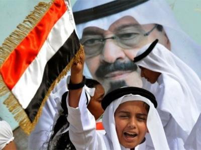 Un niño saluda el convoy que transporta al Rey saudí.-AFP