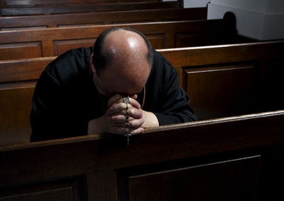 Un sacerdote reza, rosario en mano, en una iglesia de La Haya (Países Bajos).-