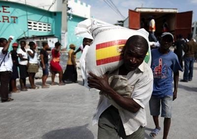 Un hombre carga un saco de la ayuda española en Puerto Príncipe (Haití).-