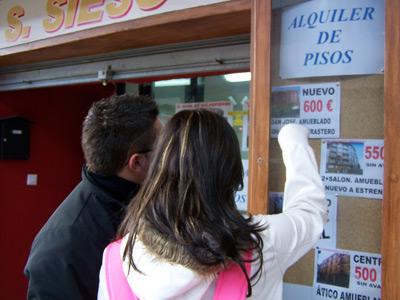 Dos jóvenes leen anuncios de alquiler de viviendas.