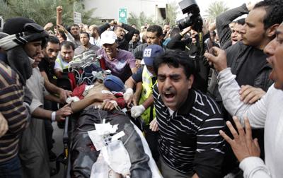 Manifestantes antigubernamentales acompañan, ayer en Manama, a uno de los heridos en el ataque de las fuerzas de seguridad.